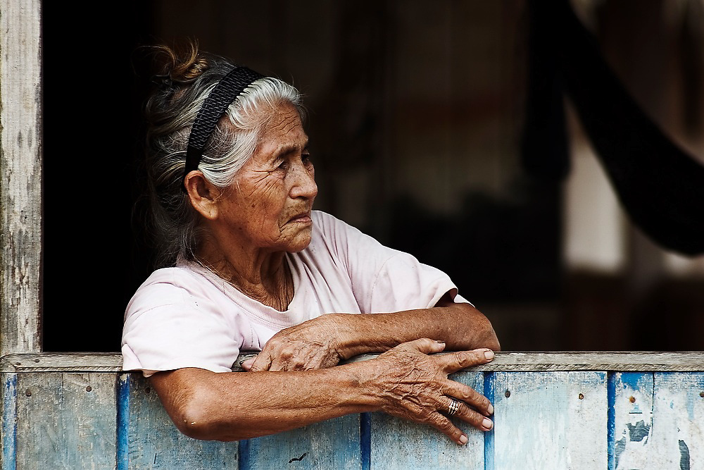 An elderly shopkeeper waits for customers at the river settlement of Boca Manu, deep inside the Manu National Park Cultural Zone, Peru.