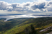 Fall foliage beginning to turn red and orange amid evergreen forests. Looking out toward the Cranberry Islands from Cadillac Mountain, Acadia National Park, Maine.