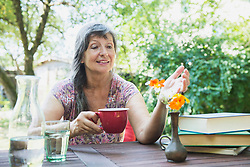 Senior woman drinking coffee while looking at fresh flower vase in the garden, Altoetting, Bavaria, Germany
