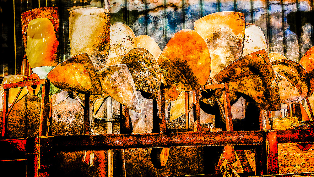 Symbols of power, a rack of fishing boat propellers weathers outside a marine repair works in a collage of colors and shadows.