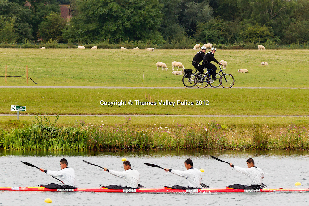 Two cycle mounted officers from Thames Valley Police patrol the lakeside at the Eton Dorney Olympic Venue during the London 2012 Games as the Chinese team prepare for their heat in the K4 1000m. Eton Dorney, UNITED KINGDOM. August 07 2012. <br /> Photo Credit: MDOC/Thames Valley Police<br /> © Thames Valley Police 2012. All Rights Reserved. See instructions.