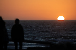 © Licensed to London News Pictures. 02/04/2020. Padstow, UK. A woman walks past the sun setting over Constantine Bay on the north coast of Cornwall after a warm clear day. Warm weather is expected next week. Photo credit : Tom Nicholson/LNP