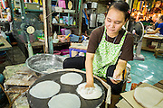 "24 AUGUST 2013 - BANGKOK, THAILAND: A woman makes ""roti"" a type of Indian flatbread popular in Southeast Asia, in Khlong Toei Market. Thailand entered a ""technical"" recession this month after the economy shrank by 0.3% in the second quarter of the year. The 0.3% contraction in gross domestic product between April and June followed a previous fall of 1.7% during the first quarter of 2013. The contraction is being blamed on a drop in demand for exports, a drop in domestic demand and a loss of consumer confidence. At the same time, the value of the Thai Baht against the US Dollar has dropped significantly, from a high of about 28Baht to $1 in April to 32THB to 1USD in August.    PHOTO BY JACK KURTZ"