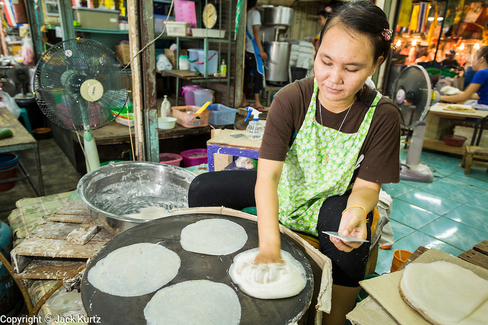 """24 AUGUST 2013 - BANGKOK, THAILAND: A woman makes """"roti"""" a type of Indian flatbread popular in Southeast Asia, in Khlong Toei Market. Thailand entered a """"technical"""" recession this month after the economy shrank by 0.3% in the second quarter of the year. The 0.3% contraction in gross domestic product between April and June followed a previous fall of 1.7% during the first quarter of 2013. The contraction is being blamed on a drop in demand for exports, a drop in domestic demand and a loss of consumer confidence. At the same time, the value of the Thai Baht against the US Dollar has dropped significantly, from a high of about 28Baht to $1 in April to 32THB to 1USD in August.    PHOTO BY JACK KURTZ"""