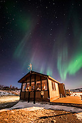 Reykjanes house with Northern lights above by night in winter, Iceland