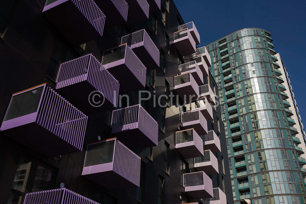 Apartment balconies of new Housing Association accomodation in the 2012 Olympic development zone built by contractor Armore. This is in east London, a kilometre south of the 2012 London Olympic Park and stadium site. Purple colour themed balconies look both modern and attractive to poorer residents in this otherwise downtrodden borough of Newham and designed and built by contractor, Ardmore for Genesis Housing Association, 150 High Street, Stratford, 704 homes, in five new residential blocks, one of which, at over 132 metres, will be one of the highest residential towers in London.