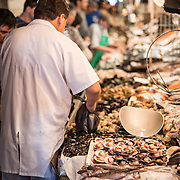 A fishmonger scoops up fresh seafood for a customer at Mercado Central de Santiago, Chile's central market. The market specializes in seafood, a staple food category of Chilean cuisine. The building is topped with an ornate cast-iron roof.