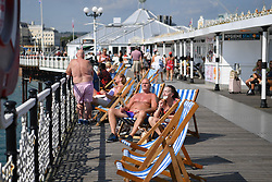 © Licensed to London News Pictures. 22/07/2021. Brighton, UK. Beachgoers enjoy the sun on Brighton pier. As COVID restrictions relax and the UK continues to open up, Brighton experiences an influx of visitors making the most of the summer heat. Meanwhile transmission of the virus continues to double every 9 days. Photo credit: Guilhem Baker/LNP