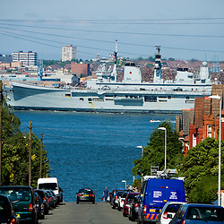 HMS Ark Royal passes some houses in Wallasey.