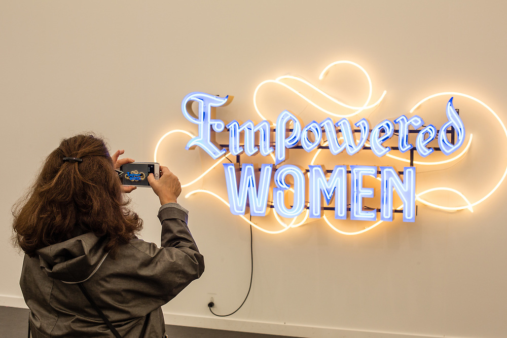 """New York, NY - May 3, 2019. A woman takes a photo of a neon scupture that reads """"Empowered Women"""" at the Frieze Art Fair on New York City's Randalls Island."""