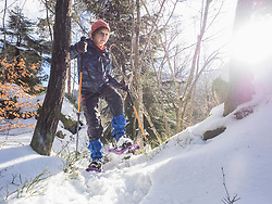 Girl snowshoeing in Black Forest under bright sunlight, Germany, Europe