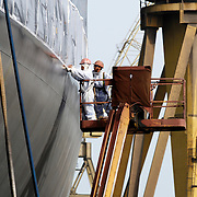 Two men working on the exterior of a ship
