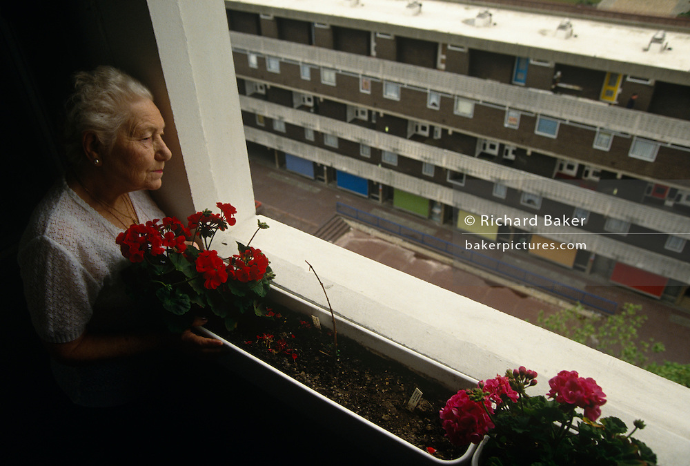 An elderly lady resident of a tower block, watches the outside world from her high-rise window, overlooking the Middlesex Estate in the City of London. A window box with geraniums is by the glass and she peeers down to a bleak urban estate, empty of human contact or friendly neighbours. She lives alone in this grim place but she is looking after herself showing brushed hair , a lace top and lipstick. The world outside is a depressingly empty landscape of concrete walkways and garage doors, an inner-city environment devoid of human interaction or friendliness..