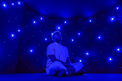 "© Licensed to London News Pictures. 27/10/2019. LONDON, UK. A staff member sits inside a meditative isolation chamber called ""Life Palace (Tea Room)"", 2013, by Tatsuo Miyajima.  Advance preview of ""24/7: A Wake-Up Call For Our Non-Stop World"", a new exhibition opening on 31 October at Somerset House.  The show examines our inability to switch off from our 24/7 culture.  Over 50 multi-disciplinary works explore the pressure to produce and consume information around the clock. taking visitors on a 24-hour cycle from dawn to dusk through interactive installations.  Photo credit: Stephen Chung/LNP"