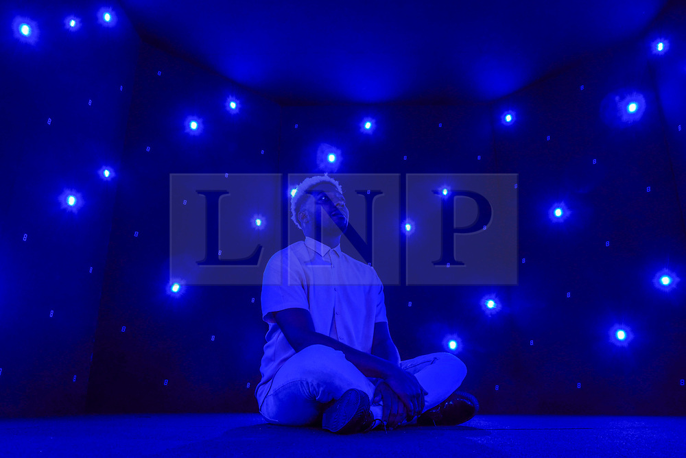 """© Licensed to London News Pictures. 27/10/2019. LONDON, UK. A staff member sits inside a meditative isolation chamber called """"Life Palace (Tea Room)"""", 2013, by Tatsuo Miyajima.  Advance preview of """"24/7: A Wake-Up Call For Our Non-Stop World"""", a new exhibition opening on 31 October at Somerset House.  The show examines our inability to switch off from our 24/7 culture.  Over 50 multi-disciplinary works explore the pressure to produce and consume information around the clock. taking visitors on a 24-hour cycle from dawn to dusk through interactive installations.  Photo credit: Stephen Chung/LNP"""