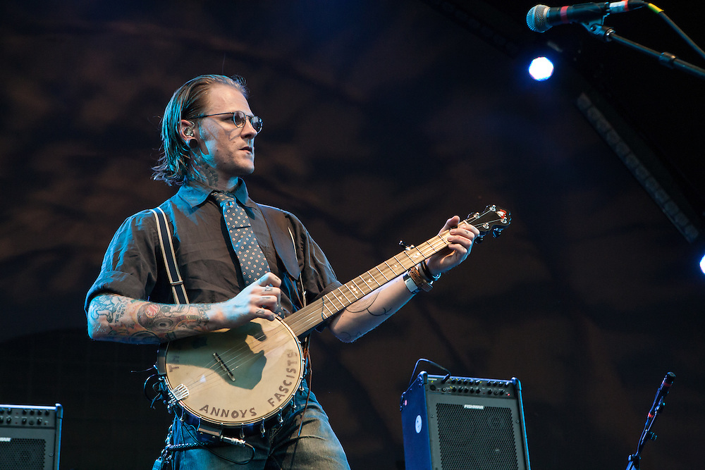 "Cooper McBean of The Devil Makes Three on stage at Celebrate Brooklyn. His banjo is captioned ""This machine annoys fascists."""