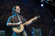 """Cooper McBean of The Devil Makes Three on stage at Celebrate Brooklyn. His banjo is captioned """"This machine annoys fascists."""""""