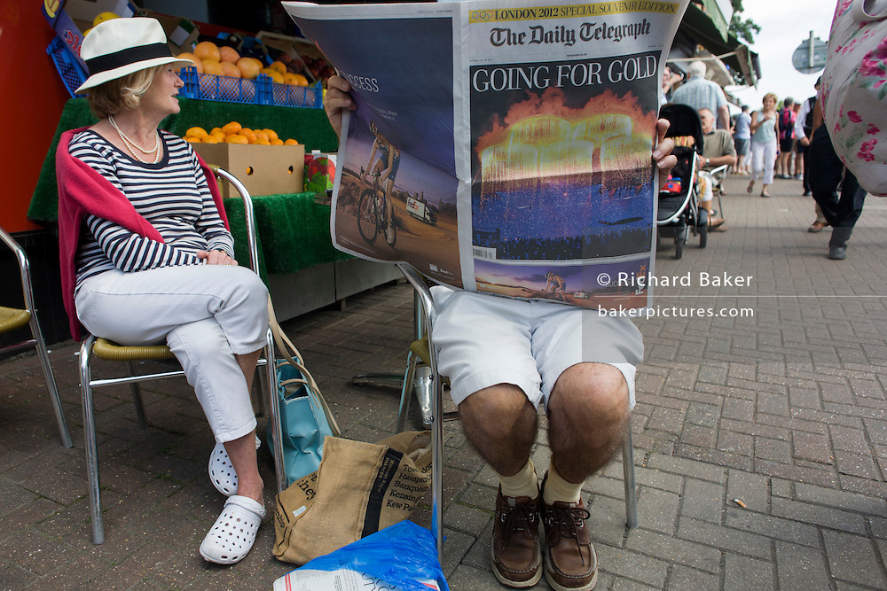 Reader of the Daily Telegraph newspaper reads about the previous night's Olympic opening ceremony,.on the first day of competition of the London 2012 Olympic 250km mens' road race. Starting from central London and passing the capital's famous landmarks before heading out into rural England to the gruelling Box Hill in the county of Surrey. Local southwest Londoners lined the route hoping for British favourite Mark Cavendish to win Team GB first medal but were eventually disappointed when Kazakhstan's Alexandre Vinokourov eventually won gold.