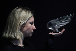 Bonhams member of staff Jessie Bromovsky holding a 'Victoire' car mascot, designed in 1928 and valued between £10,000-£15,000, during a photo call for a private collection of masterpieces by glassmaker Rene Lalique before it is offered at auction at Bonhams in London.