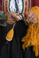 Old woman in traditional dress and hat spinning wool, Chinchero, Department of Cuzco, Peru, South America   MR, PR