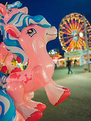 United States, Washington, Puyallup, inflatable toy prize and ferris wheel at annual Puyallup Fair at dusk