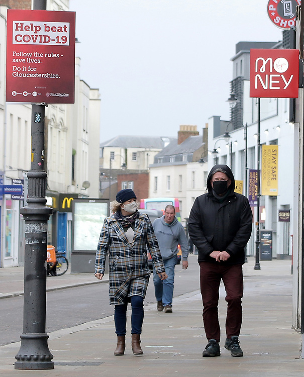 20th Feb 2021. Cheltenham, England. A man and woman walk through Cheltenham town centre wearing face covering's during the countries third national lockdown.