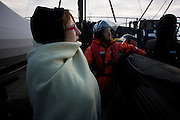 Nicola Paris and Molly Kendall, from left, watch the horizon for the Sea Shepherd helicopter's return after a scouting mission to find the Japanese whaling fleet. (Photo by Adam Lau)
