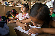 """25 FEBRUARY 2008 -- MAE SOT, TAK, THAILAND: The children of Burmese migrants take classes at the Blue Sky School near the garbage dump in Mae Sot, Thailand. The students at the school are all the children of Burmese migrants who work in the garbage dump, sorting and selling what they find amid the trash. There are millions of Burmese migrant workers and refugees living in Thailand. Many live in refugee camps along the Thai-Burma (Myanmar) border, but most live in Thailand as illegal immigrants. They don't have papers and can not live, work or travel in Thailand but they do so """"under the radar"""" by either avoiding Thai officials or paying bribes to stay in the country. Most have fled political persecution in Burma but many are simply in search of a better life and greater economic opportunity.  Photo by Jack Kurtz"""
