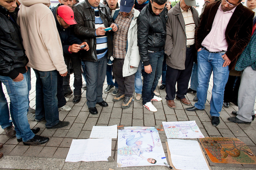 Tunis, Tunisia. January 27th 2011.People watch humoristic political drawings made by a man on the Avenue Bourguiba..A daily life scene outside the protests places, thirteen days after the ousted president Zine El Abidine Ben Ali fled the country.....