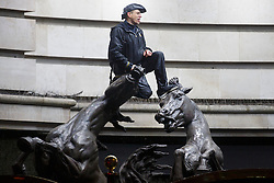 © licensed to London News Pictures. London, UK 01/01/2014. A man climbs on top of The Four Bronze Horses of Helios on Haymarket, London whilst celebrating the New Year at the first hours of 2014. Photo credit: Tolga Akmen/LNP