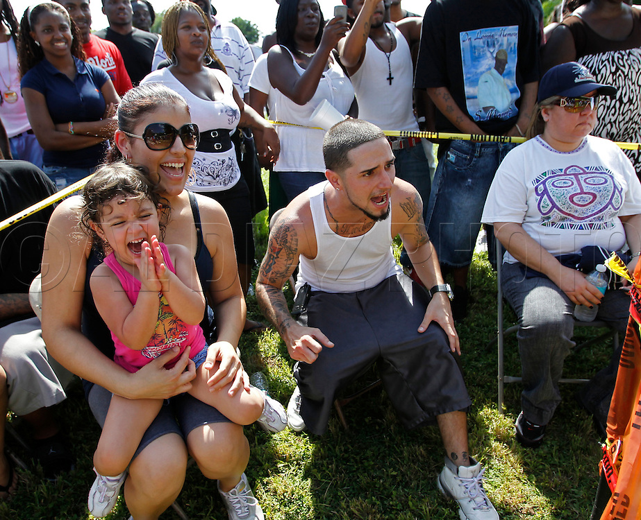 """Sandy Ogaza with her daughter Jolee Rivero, 3, and Jorge Guerra at right, cheer on the fighters on September 18, 2010. Dhafir Harris, """"Dada 5000"""", puts on backyard fights at his mother house, which go viral on youtube and have been the subject of documentaries. Sometimes the men fight until they are unconscious. There' s no gloves and occasionally, there's a cage. The community has taken to the events, because they are able to set up businesses selling food and washing cars."""