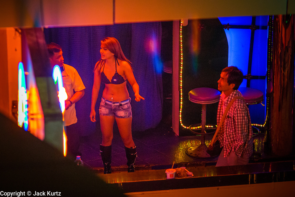 "19 JANUARY 2013 - BANGKOK, THAILAND:   A sex worker talks to a man in front of a bar in the Nana Entertainment Plaza in Bangkok. Prostitution in Thailand is technically illegal, although in practice it is tolerated and partly regulated. Prostitution is practiced openly throughout the country. The number of prostitutes is difficult to determine, estimates vary widely. Since the Vietnam War, Thailand has gained international notoriety among travelers from many countries as a sex tourism destination. One estimate published in 2003 placed the trade at US$ 4.3 billion per year or about three percent of the Thai economy. It has been suggested that at least 10% of tourist dollars may be spent on the sex trade. According to a 2001 report by the World Health Organisation: ""There are between 150,000 and 200,000 sex workers (in Thailand).""       PHOTO BY JACK KURTZ"