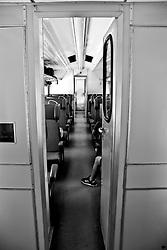 corridoio che attraversa gli scompartimenti della littorina. Reportage che analizza le situazioni che si incontrano durante un viaggio lungo le linee ferroviarie delle Ferrovie Sud Est nel Salento