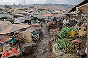 After a brief downpour paths become muddy and slippery in Kalerwe Market, Kampala, Uganda.