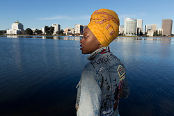 """Oakland, Calif. native Brittani Sensabaugh poses by Lake Merritt, Friday, Jan. 27, 2017. Sensabaugh, a documentary photographer who has featured work from """"forgotten cities"""" around the globe, got frustrated seeing the negative billboards in her neighborhood--so she decided decided to fundraise a project to put positive imagery on local billboards, emphasizing black communities, healthy eating, and how """"love is more powerful than fear."""" (Photo by D. Ross Cameron)"""