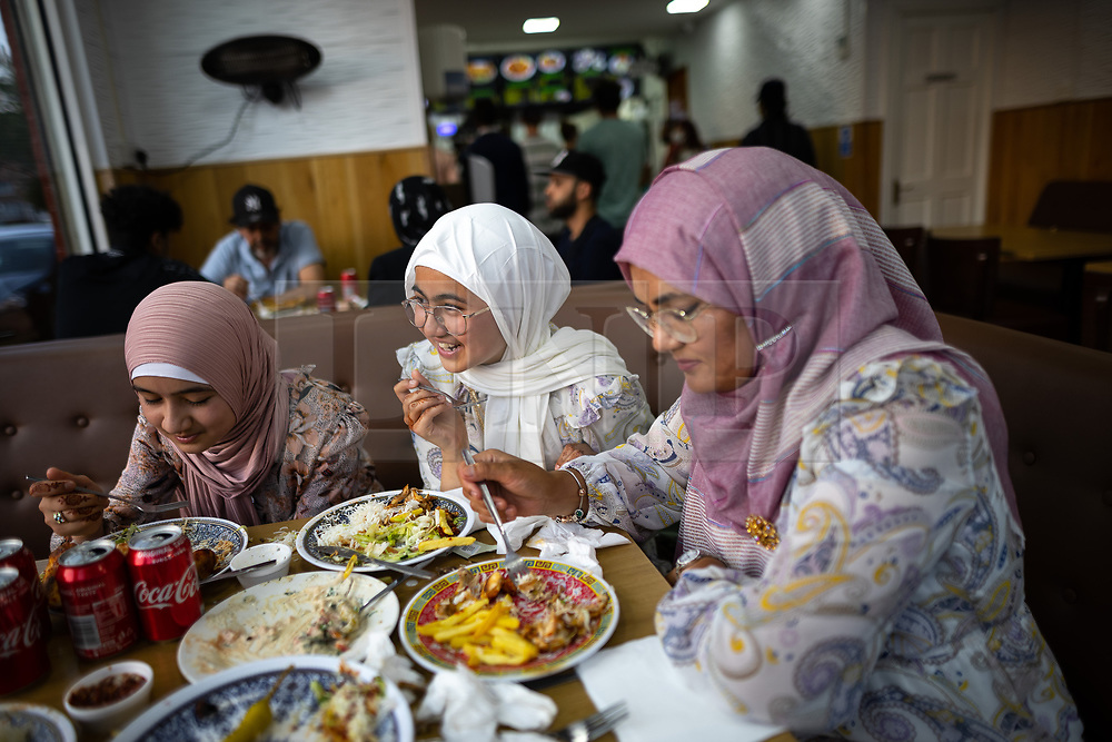 © Licensed to London News Pictures. 20/07/2021. Manchester, UK. Visitors from Blackpool enjoy an evening meal . Muslims celebrate Eid al-Adha in Rusholme in Manchester. The festival marks the Islamic tale of the prophet Ibrahim , who offered his son as a sacrifice to Allah . Photo credit: Joel Goodman/LNP