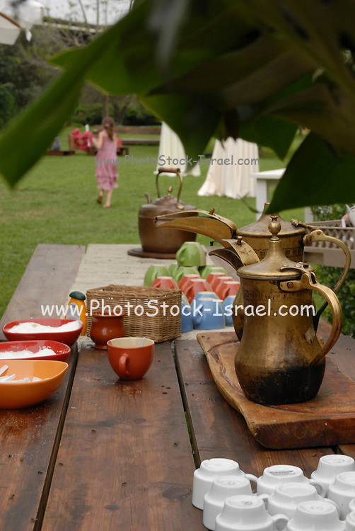 Table set for coffee at an outdoor banquet with Mideastern copper coffe jug