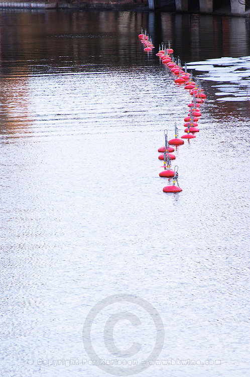 Karlbergskanalen water in winter between Kungsholmen and Vasastan. A curved line of red buoys to moor boats and some iceflakes ice flakes Stockholm, Sweden, Sverige, Europe