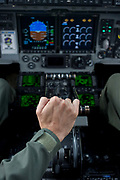 A pilot of the US Air Force holds the throttle levers in the cockpit of a C-17 transport jet at the Farnborough Air Show, UK. The Boeing C-17 Globemaster III is a large military transport aircraft. It was developed for the United States Air Force (USAF) from the 1980s to the early 1990s by McDonnell Douglas; the company later merged with Boeing. The C-17 is used for rapid strategic airlift of troops and cargo to main operating bases or forward operating bases throughout the world. It can also perform tactical airlift, medical evacuation and airdrop missions. The Farnborough International Airshow is a seven-day international trade fair for the aerospace industry and held every two years in mid-July at Farnborough Airport in Hampshire, England known as the home of British aviation, held since there since 1948.