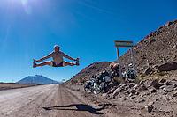 Cyclist jumping at Paso Fronterizo Ascotan, north Chile