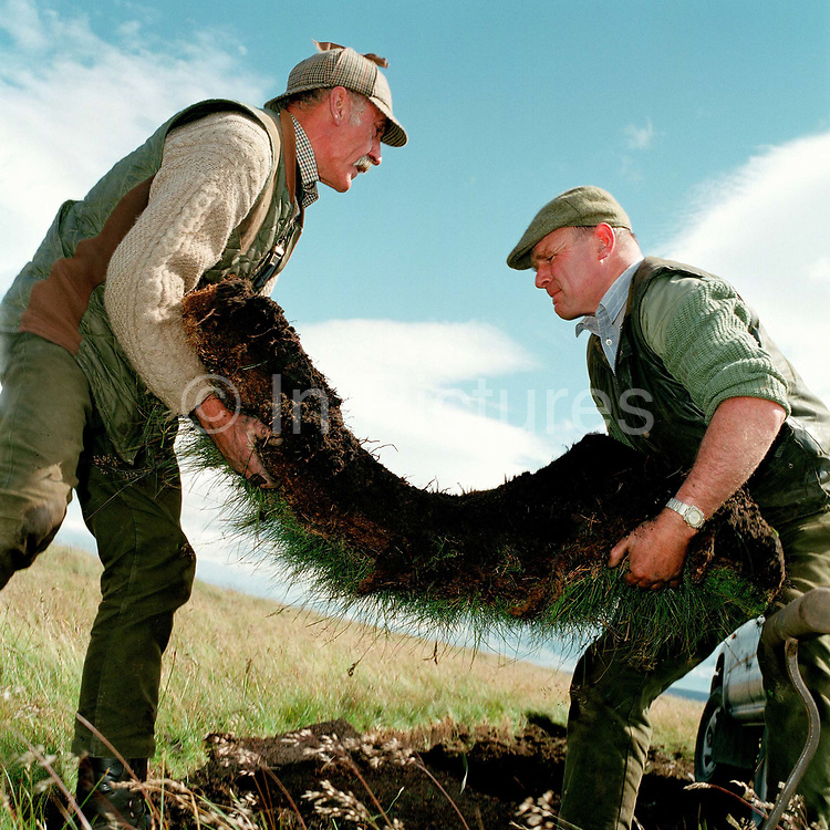 Gamekeepers Niel Pearson and Don Herd lift turf from the moor to turf shooting butts for the Middlesmoor grouse shoot, Upper Nidderdale, North Yorkshire, UK
