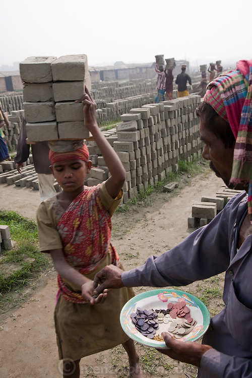 A child receives a token for carrying bricks at the JRB brick factory near Sonargaon, outside Dhaka, Bangladesh. The heavy clay soils along the river near the market town of Sonargaon are well suited for making bricks. At the JRB brick factory, workers of all ages move raw bricks from long, stacked rows, where they first dry in the sun, to the smoky coal-fired kilns. After being fired, the bricks turn red. A foreman keeps tally, handing the workers colored plastic tokens corresponding to the number of bricks they carry past him. They cash in the chips at the end of each shift, taking home the equivalent of $2 to $4 (USD) a day.