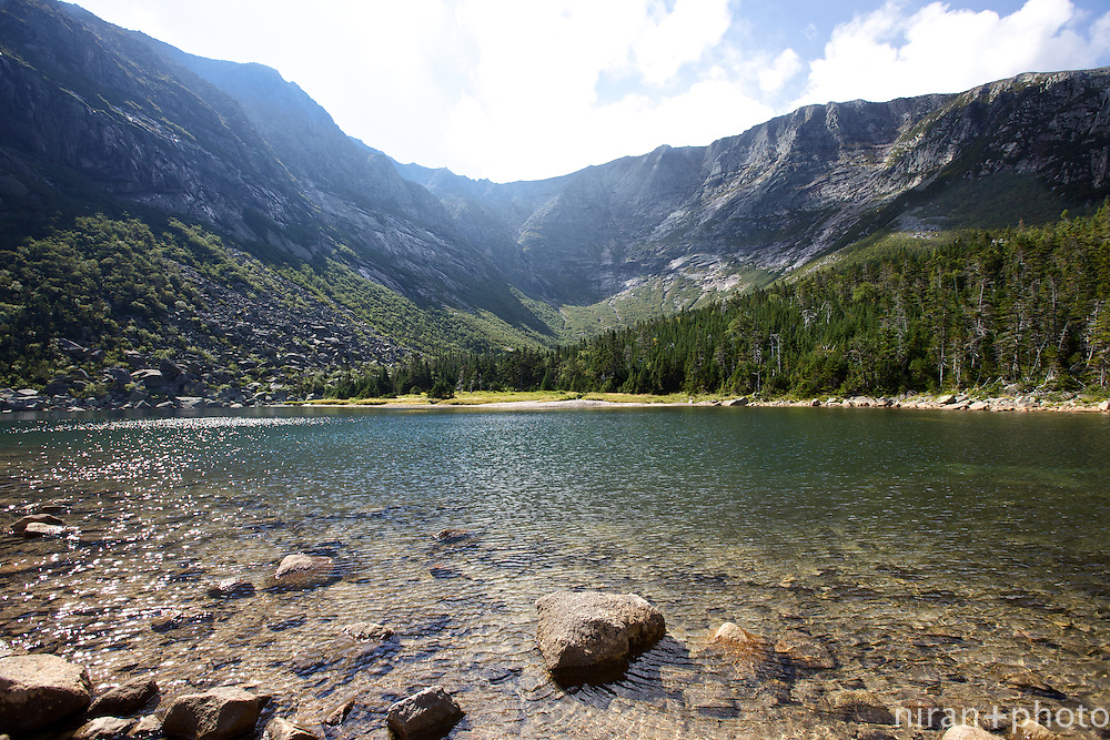 A shot of Chimney pond with the sun just starting to peak from behind the mountain.