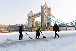 © Licensed to London News Pictures. 28/02/2018. London, UK. Workers clear snow with shovels in front of Tower Bridge this morning. London has experienced heavy snow fall and freezing weather overnight. Photo credit: Vickie Flores/LNP