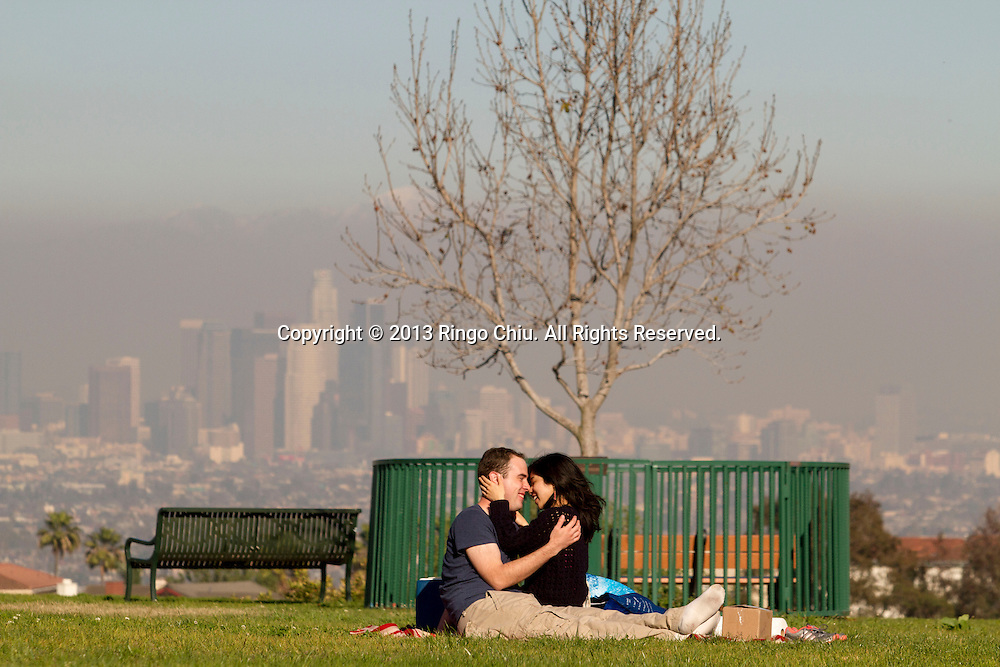 Robert Lanford 27, of Glendale, celebrates Valentine's Day with his girl friend Liane Uehara, 28, of Burbank, in Kenneth Hann Park as background is Downtown Los Angeles Skyline on Thursday Feburary 14, 2013. The smog is visible in downtown Los Angeles on a late afternoon.(Photo by Ringo Chiu/PHOTOFORMULA.com).