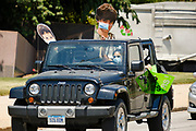 """24 JULY 2020 - DES MOINES, IOWA: A teacher holds up a picture of one of her children as she drives around the Iowa State Capitol during a motorcade to protest the reopening of Iowa schools. Hundreds of teachers from across Iowa came to the state capitol Friday to protest Governor Kim Reynolds' order that school must reopen with in person education and minimized the potential for """"distance learning."""" The event was one of the largest COVID-19 protests in Iowa since the pandemic started, more than 740 teachers signed up to attend the protest. After the protest officially ended, many teachers left the capitol and drove to Gov. Reynolds' residence, where they drove around her mansion and honked horns. Some people left notes on the entrance to the governor's residence. Gov. Reynolds ordered the school reopening last week, but according to teachers, the state has not implemented health guidelines or bought protective equipment like face masks in the quantity required to slow the spread of the Coronavirus (SARS-CoV-2). Iowa's numbers of COVID-19 infections are up statewide.          PHOTO BY JACK KURTZ"""