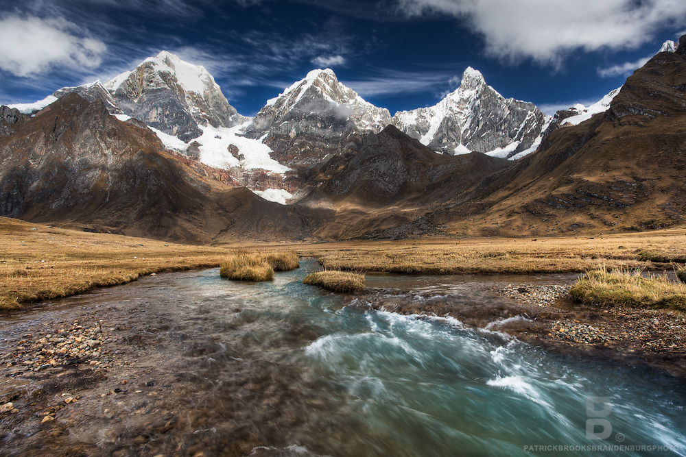 A turquoise river with motion blur and subdued rich yellow grass in the foreground of the enormous peaks of Yerupaja Grande and Chico, and Jirishanca to the right in the Cordillera Huayhuash of the Andes Mountains of Peru. A polarizer intensifies the clouds and darkens the blue sky.