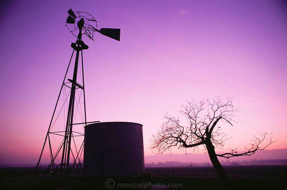 Farm windmill (broken) and water tank against the magenta dusk sky at Sutter Buttes (world's smallest mountain range). California.