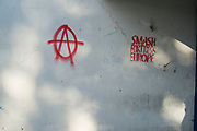 Anarchy symbol anarchist graffiti calling to smash fortress Europe in Whitechapel in London, England, United Kingdom.