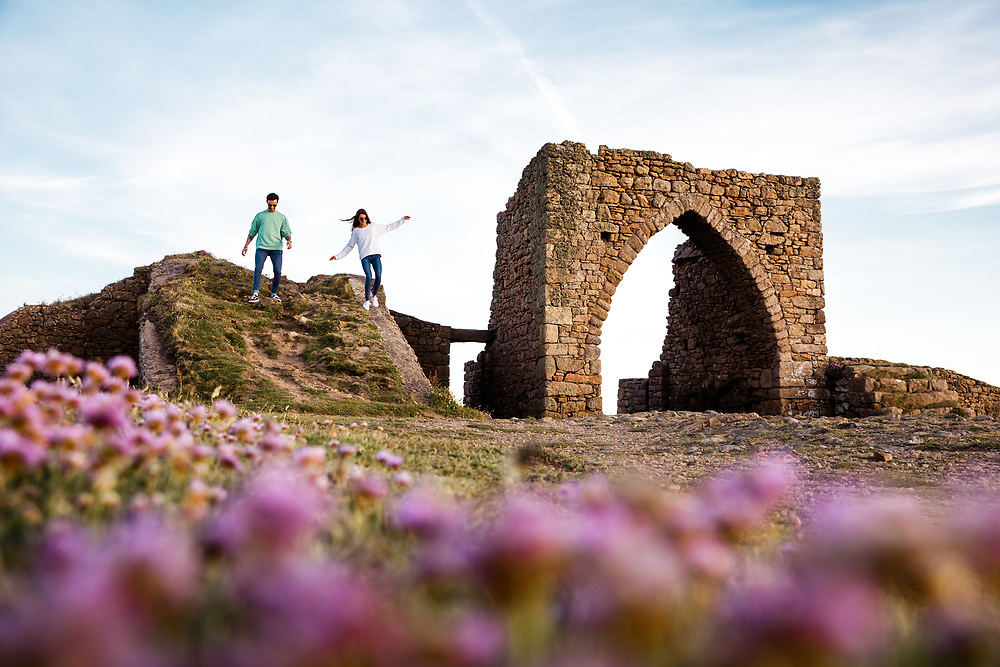 View through pink flowers of a couple exploring the historic ruins of the tourist attraction, Grosnez Castle, on the north coast of Jersey, Channel Islands